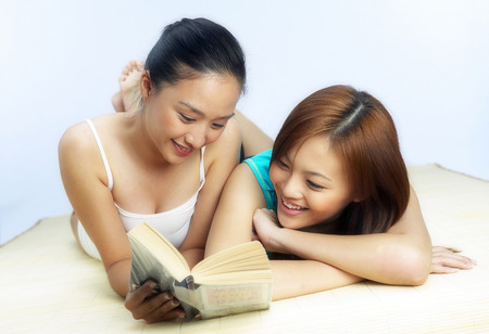tied down: Two women lying on the bed reading book together