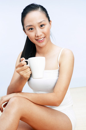 energized: Woman in white holding a cup of coffee LANG_EVOIMAGES