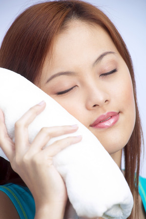 perspiring: Close-up picture of woman enjoying a wet warm towel on her face LANG_EVOIMAGES