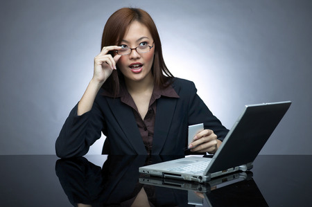 bespectacled: Bespectacled business woman doing work on the laptop