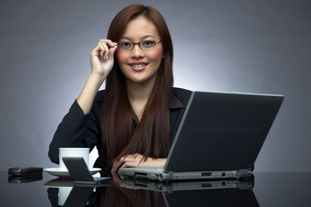 bespectacled: Bespectacled business woman posing at her table