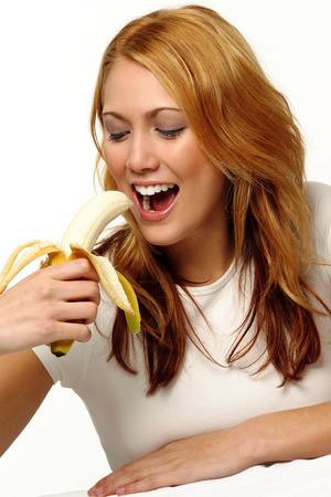 peeled banana: Studio shot of woman eating a peeled banana