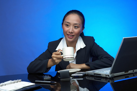 time off: Business woman taking some time off to drink coffee