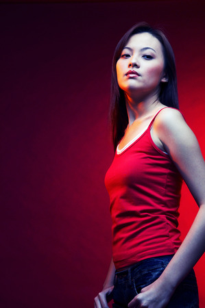 spaghetti strap: Woman in red top posing on a red background LANG_EVOIMAGES