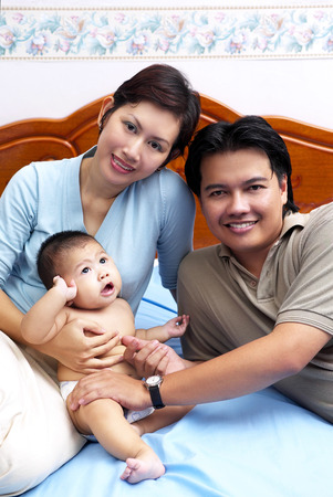 motherly love: Parents and a baby posing on the bed