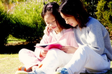 reading book: Two girls reading book in the park LANG_EVOIMAGES