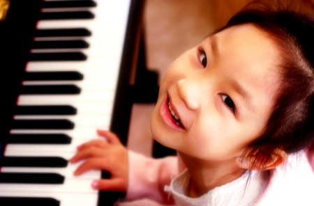Top angle view of young girl playing piano LANG_EVOIMAGES
