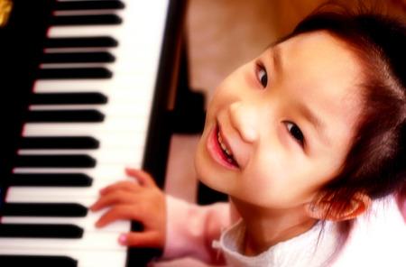 tocando el piano: Vista superior del ángulo de la niña tocando el piano