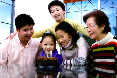 her: Girl sitting in front of her birthday cake with her family members surrounding her