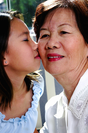 grandkids: Girl giving her grandmother a peck on the cheek LANG_EVOIMAGES