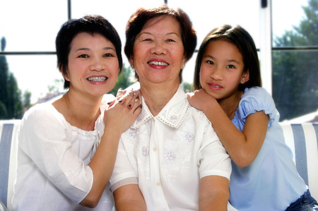 Girl posing with her mother and grandmother