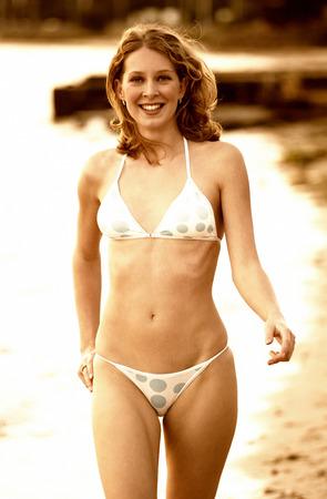 Woman in bikini walking along the beach