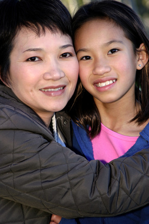 her: Close-up picture of woman hugging her daughter LANG_EVOIMAGES