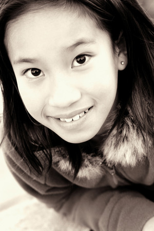 lass: Sepia picture of a girl in jacket smiling at the camera