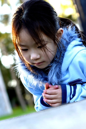 peaking: Girl in hooded jacket daydreaming LANG_EVOIMAGES