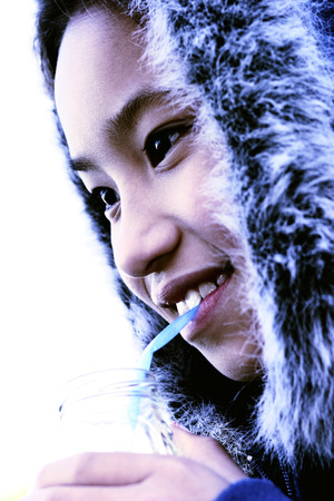 furry: Close-up picture of a young girl in furry jacket drinking water
