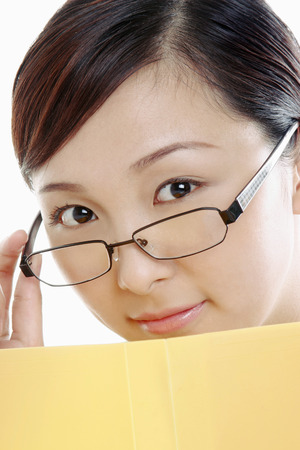 bespectacled: Bespectacled woman holding document while looking at the camera.