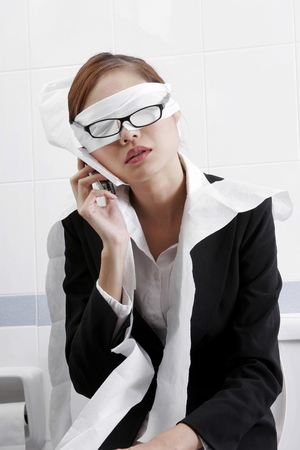 Businesswoman making an emergency calls in the toilet. Stock Photo