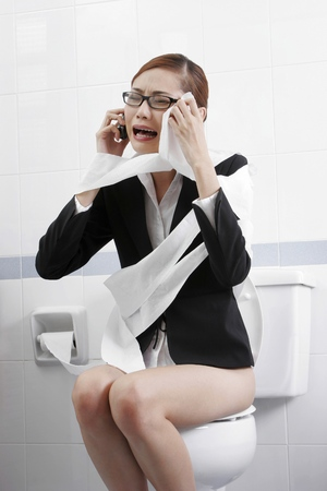 Businesswoman crying while making an emergency calls in the toilet.