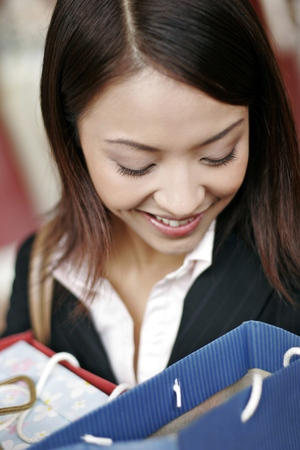 retail therapy: Businesswoman smiling while looking into her paper bags. LANG_EVOIMAGES