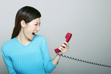 receiver: Woman screaming into phone receiver. LANG_EVOIMAGES