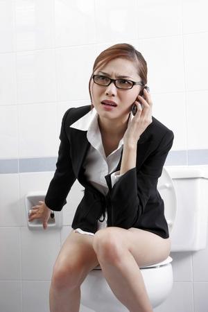 Geschäftsfrau, die einen Notruf in der Toilette. LANG_EVOIMAGES