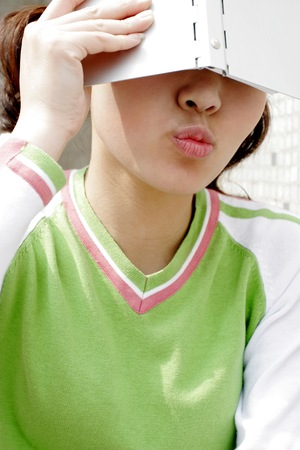 Girl puckering lips while covering her face with an organizer.