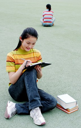 revision book: Girl revising her school work.