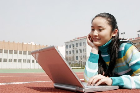 sports track: Girl lying forward on the sports track using laptop. LANG_EVOIMAGES