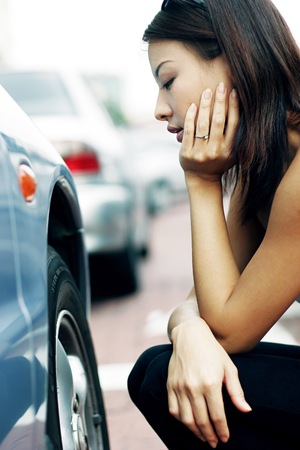 Woman looking at the flat tire with frustration. 写真素材