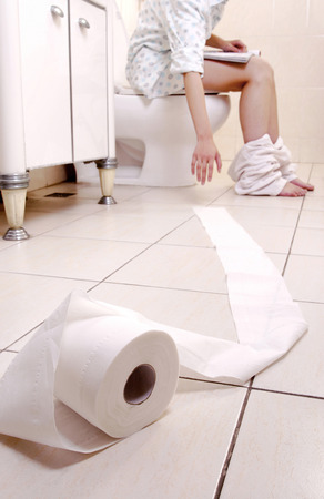 Woman reaching for toilet roll as she sits on the toilet.