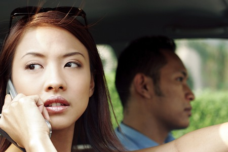 he she: Woman talking on the phone while sitting in the car.