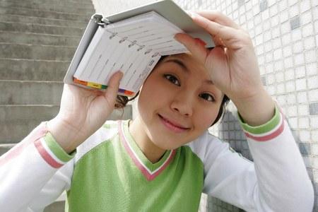 shielding: Girl shielding her face with an organizer.
