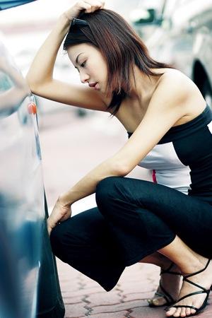en cuclillas: Una mujer mirando a la llanta desinflada con la frustración.