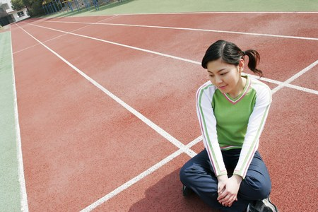 sports track: Girl sitting on the sports track.
