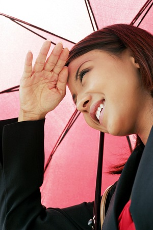 shielding: Businesswoman shielding her eyes while holding an umbrella. LANG_EVOIMAGES
