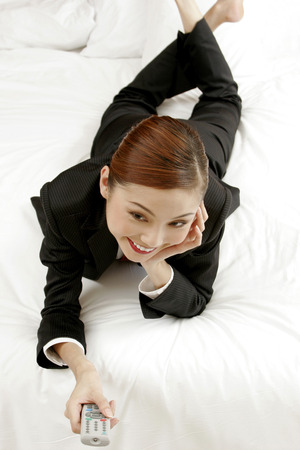 lying forward: Businesswoman lying forward on the bed channel surfing.