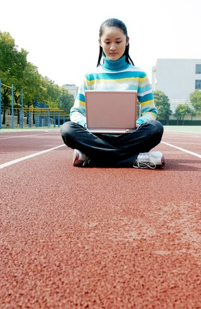sports track: Girl sitting on the sports track using laptop.