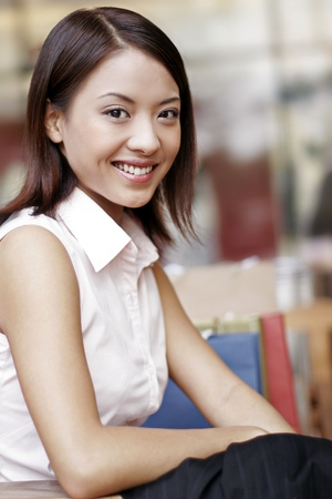 retail therapy: Businesswoman smiling at the camera. LANG_EVOIMAGES