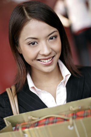 retail therapy: Businesswoman smiling while holding a paper bag.