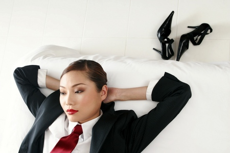 Businesswoman relaxing on the bed.