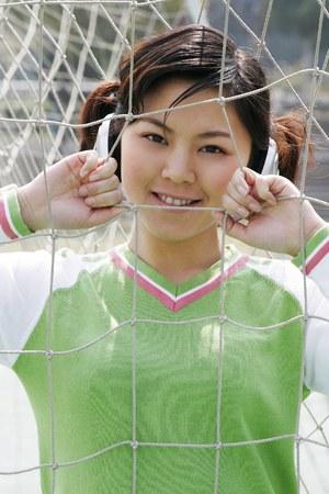 sensory perception: Girl with headphones posing behind the goal net.