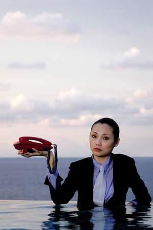 Businesswoman in suit holding a telephone.