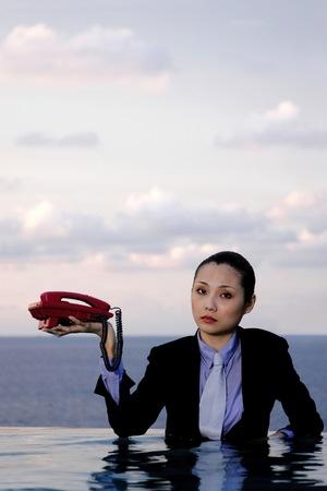 Empresaria en el juego que sostiene un teléfono.