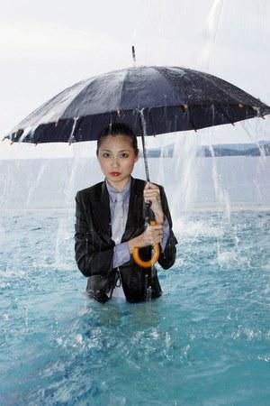 Zakenvrouw in pak bedrijf een paraplu in het zwembad.