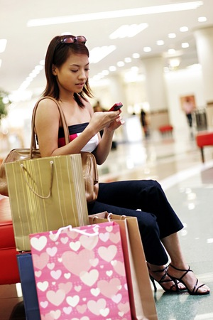 retail therapy: Woman sitting with her paper bags text messaging on the phone.