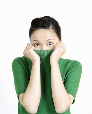 covering mouth: Woman with shirt covering mouth.