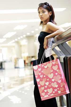 retail therapy: Woman standing in the mall holding paper bags.