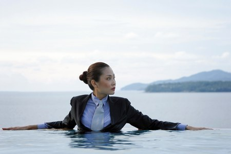 Businesswoman in suit sitting in the swimming pool.