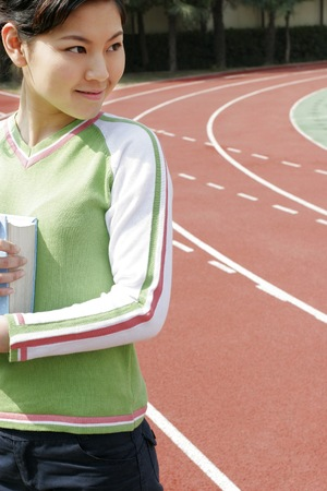 revision book: Girl standing on the track holding a book.